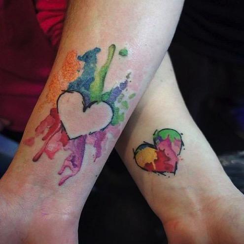 Lesbian tattoo, matching LGBTQ rainbow heart tattoo on wrist