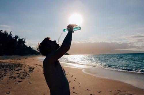 stress free travel tips, man drinking water